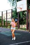Glückliche junge Frau des Porträts, die Basketball auf Gericht im Freien hält lizenzfreies stockbild