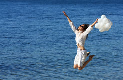 Glückliche junge Frau, die über das Meer springt Stockfotos