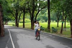 Glückliche junge Frau, die über Fahrrad sich entspannt Stockfoto