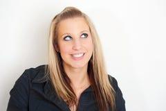 Glückliche junge Frau, die über weißer Wand lächelt Lizenzfreies Stockbild