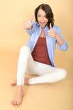 Glückliche junge Frau, die auf Boden mit den Daumen oben sitzt Stockbilder