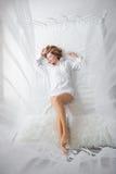 Glückliche junge Frau, die auf dem Bett liegt stockfotografie