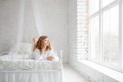 Glückliche junge Frau, die auf dem Bett liegt stockbilder
