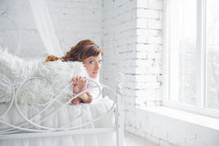 Glückliche junge Frau, die auf dem Bett liegt lizenzfreie stockbilder
