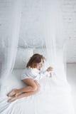 Glückliche junge Frau, die auf dem Bett liegt stockbild