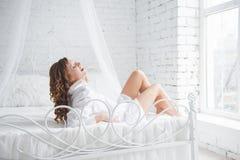 Glückliche junge Frau, die auf dem Bett liegt lizenzfreies stockbild