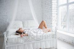 Glückliche junge Frau, die auf dem Bett liegt stockfotos