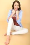 Glückliche junge Frau, die auf dem Boden mit den Daumen oben sitzt Stockfotos