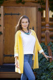 Glückliche junge Frau, die auf dem Portal eines Holzhauses steht Lizenzfreies Stockfoto