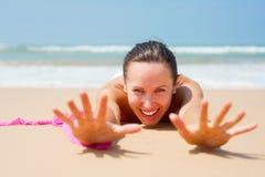 Glückliche junge Frau, die auf dem Sand liegt Stockbild