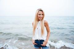 Glückliche junge Frau, die auf dem Strand steht und lächelt Lizenzfreies Stockfoto