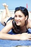 Glückliche junge Frau, die auf dem Strandlächeln legt lizenzfreie stockbilder
