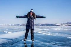Glückliche junge Frau, die auf den gefrorenen Baikalsee eisläuft Stockfoto