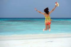 Glückliche junge Frau, die auf den Strand springt lizenzfreies stockfoto