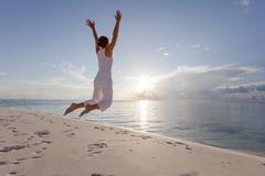 Glückliche junge Frau, die auf den Strand springt Stockbild