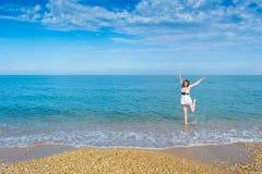Glückliche junge Frau, die auf den Strand springt stockfotografie