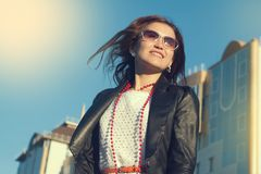 Glückliche junge Frau, die auf eine Stadtstraße geht lizenzfreie stockfotografie
