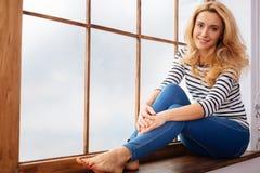 Glückliche junge Frau, die auf einem Fensterbrett sitzt Lizenzfreie Stockbilder