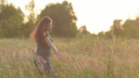 Glückliche junge Frau, die auf einem Gebiet geht und die Anlagen mit seiner Hand streicht stock video