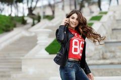 Glückliche junge Frau, die auf Handy spricht Stockbilder