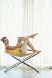 Glückliche junge Frau, die auf modernem Stuhl sitzt Lizenzfreie Stockbilder