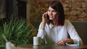 Glückliche junge Frau, die auf Sofa in den gemütlichen Stoffen mit Tasse Kaffee sitzt stock video footage