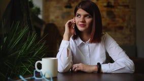 Glückliche junge Frau, die auf Sofa in den gemütlichen Stoffen mit Tasse Kaffee sitzt stock video