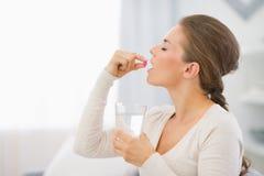 Glückliche junge Frau, die auf Sofa sitzt und Pille einnimmt Stockfoto
