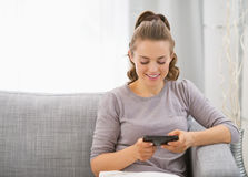 Glückliche junge Frau, die auf Sofa sitzt und sms schreibt Lizenzfreie Stockfotografie
