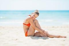 Glückliche junge Frau, die auf Strand sitzt Stockfotos