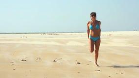 Glückliche junge Frau, die auf Strand springt stock footage