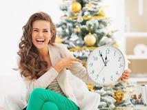 Glückliche junge Frau, die auf Uhr vor Weihnachtsbaum zeigt Stockbilder