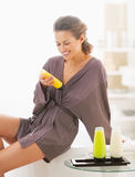 Glückliche junge Frau, die Badkosmetik im Badezimmer überprüft Stockfotografie