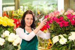 Glückliche junge Frau, die Blumen-Blumengeschäft anordnet Stockbilder