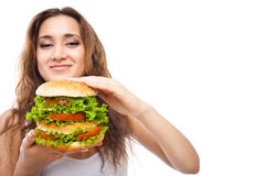 Glückliche junge Frau, die den großen leckeren Burger lokalisiert isst Lizenzfreie Stockfotografie