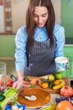 Glückliche junge Frau, die den Kuchen mit Sahne schmiert eine Schicht steht in der Küche macht lizenzfreie stockbilder