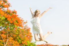 Glückliche junge Frau, die in den Park mit ihren Armen in der Luft springt lizenzfreie stockfotos