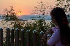 Glückliche junge Frau, die den Sonnenuntergang über dem See aufpassend steht Lizenzfreies Stockbild