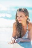 Glückliche junge Frau, die an der Küste legt Stockbild