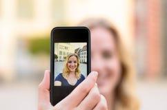 Glückliche junge Frau, die draußen ein selfie nimmt Stockfoto