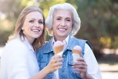 Glückliche junge Frau, die draußen Eiscreme mit alter Mutter genießt Lizenzfreie Stockfotografie