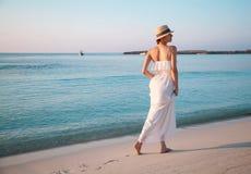 Glückliche junge Frau, die durch den Strand geht Stockfotos