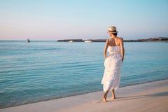 Glückliche junge Frau, die durch den Strand geht Stockbild