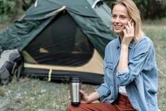 Glückliche junge Frau, die durch Mobiltelefon in der Natur spricht Stockfoto