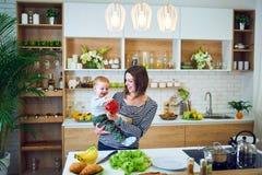 Glückliche junge Frau, die ein einjähriges Kind hält und zusammen in der Küche kocht lizenzfreie stockfotos