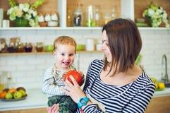 Glückliche junge Frau, die ein einjähriges Kind hält und zusammen in der Küche kocht stockfotografie