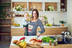 Glückliche junge Frau, die ein einjähriges Kind hält und zusammen in der Küche kocht stockfotos