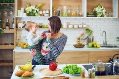 Glückliche junge Frau, die ein einjähriges Kind hält und zusammen in der Küche kocht stockbilder