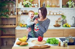 Glückliche junge Frau, die ein einjähriges Kind hält und zusammen in der Küche kocht stockbild