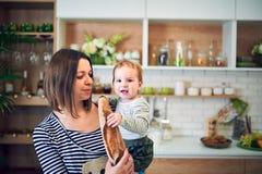 Glückliche junge Frau, die ein einjähriges Kind hält und zusammen in der Küche kocht lizenzfreies stockbild